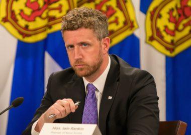 Nova Scotia Premier Iain Rankinn sits at a podium at a press conference with flags behind him.