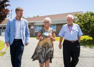 A woman walks between two men down a driveway on a sunny day