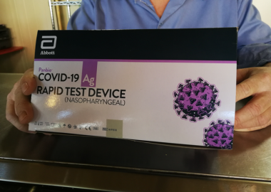 A close up of a white, black and purple COVID-19 rapid test kit box that someone is holding.