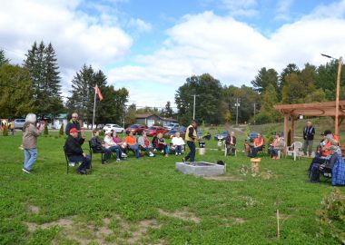 A group of people seated in lawn chairs around a fire, most wearing orange .