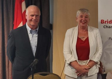 A male and female politician stand in front of a table with a microphone with a Canada flag behind them