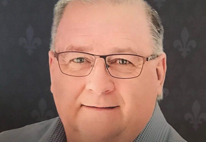 Rodrigue Vigneault, cheveux gris et chemise grise, portant des lunettes.