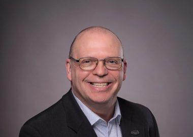 Roger LeBlanc souriant vêtu d'un veston noir et d'une chemise blanche