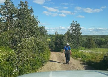 Rory Fraser walking along a dirt road in the distance.