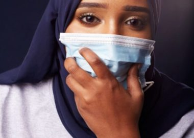 A young woman in a hijab holding a mask to her face