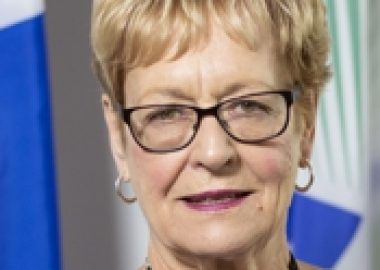 A professional headshot of Shawville Mayor Sandra Murray, wearing a purple shirt and glasses, standing in front of a Quebec flag.