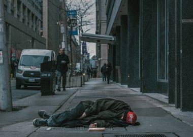 Une personne dort sur le trottoir d'une grande ville. Les passants y sont indifférents.