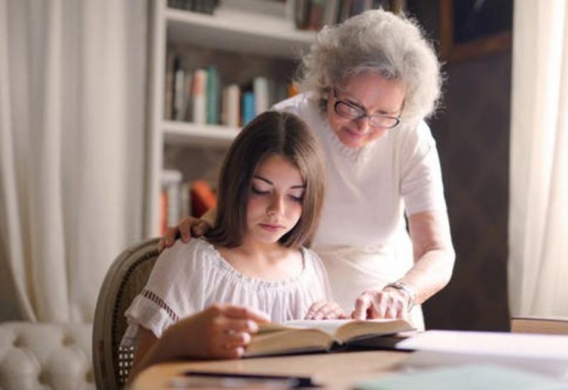 Une aînée et une jeune lisent ensemble