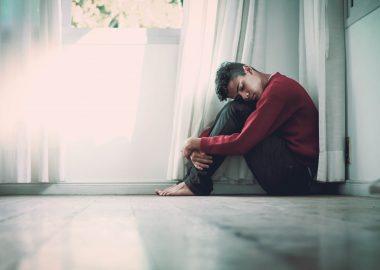 Un homme déprimé et recroquevillé sur lui-mêmedevant une fenêtre