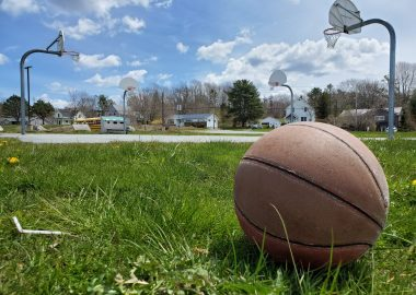 A basketball is seen on the left side of a grassy field with a basketball court and blue sky in the distance.
