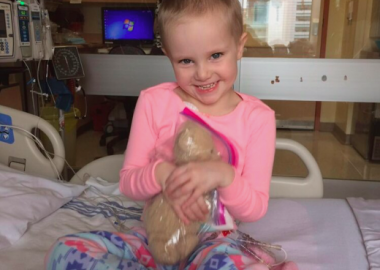 Hayden Foulon sitting in her pajamas and hugging her teddy bear in the hospital.