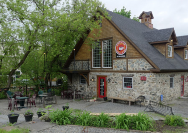 A picture of the outside of the old historic rock building The Star Cafe occupies. The building is situated beside the river.