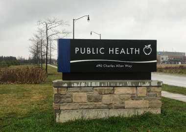 A navy WDG Public Health sign outside out front of their Fergus location on the grass on a cloudy day
