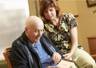 Une infirmière est assise à côté d'un résident qui lit une carte.
