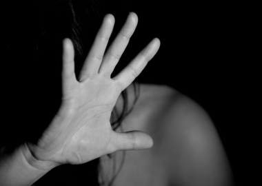 A woman holds up a hand to the camera in a black and white photo