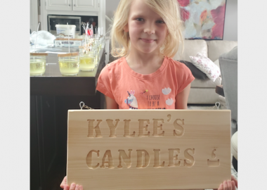 7-year-old Kylee Johnson holds a wooden sign that reads