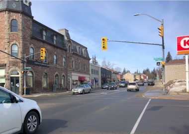 The intersection of St. David Street North and St. Andrew Street in Fergus is seen on a sunny day with a white car on the left waiting at the intersection light.