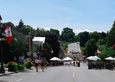 A wide shot of the main street in downtown Elora on a sunny day with tents and vendors seen at a distance
