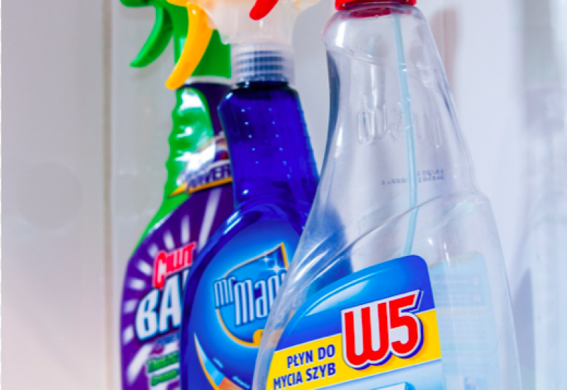 A vertical shot of three, multicoloured cleaning bottles with nozzles sitting on a glass shelf.