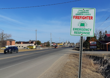 A sign about firefighter green lights next to the highway near Fergus, Ontario on a sunny day
