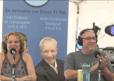 Michèle et Randy tous les deux habillés en gris sont assit devant un micro avec des écouteurs.