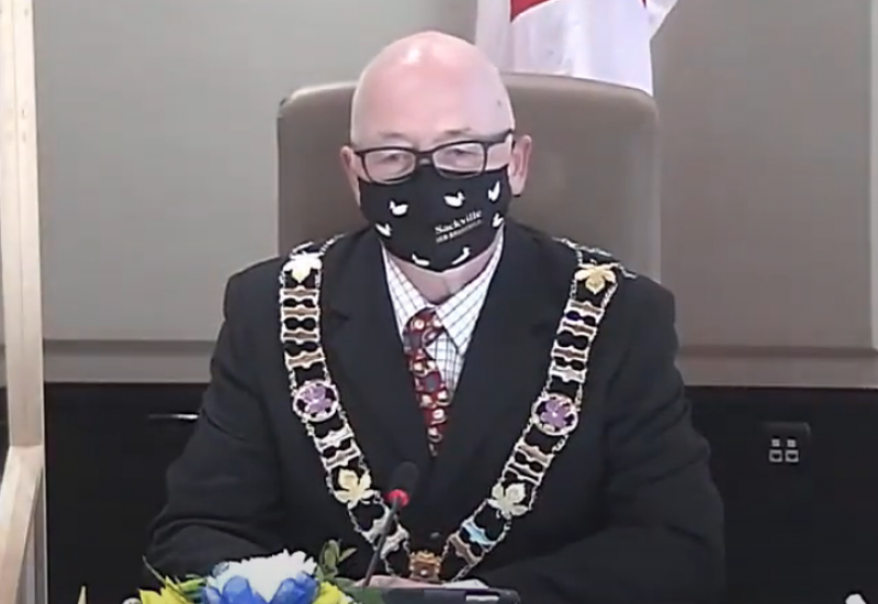 A man in a COVID-19 mask sits behind a desk