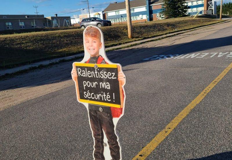 Silhouette flexible d'un enfant garçon tenant une affiche écrit: Ralentissez pour ma sécurité sur une rue avec les écoles de quartier derrière.