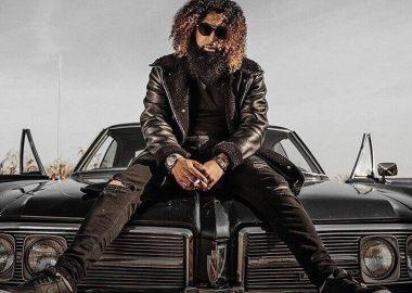 L'artiste 4Say cheveux et barbe bouclés, lunettes noires, veston en cuir, assis sur le capot d'une voiture noire
