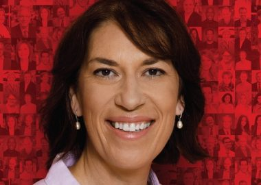 A professional headshot on a red background of Pontiac Liberal candidate Sophie Chatel.