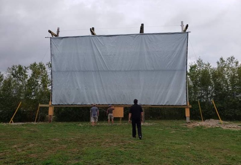 A large white movie drive-in screen is seen in a field with a man standing in front of it looking up at it on an overcast day.