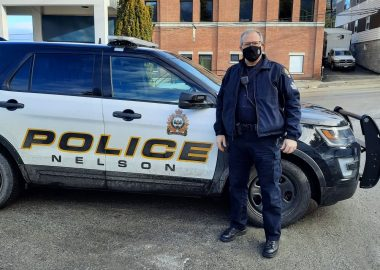 A police officer in mask in front of patrol car