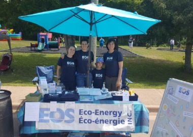 EOS Eco-Energy members stand at a booth with pamphlets.
