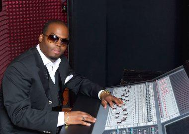 Steve Pageot en complet, chemise blanche et lunettes noires devant sa console dans son studio