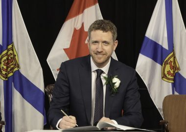 Iain Rankin writes in a book at a podium at a press conference with Nova Scotia flags behind him