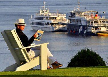 Femme assise dans une chaise blanche à l'extérieur sur un tapis de gazon. Dame portant un chapeau blanc, chandail noir, pantalon blanc et sandales à talons. Au loin arbuste, fleuve Saint-Laurents et deux bateaux de croisières.