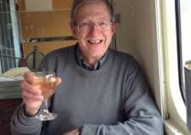 A man is seen on a train holding up a glass of white wine.