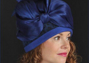 Une femme portant un chapeau bleu foncé muni d'une grosse boucle