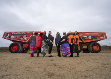 Indigenous women wearing colorful ribbon skirts in front of the two painted haul trucks used in industrial setting.