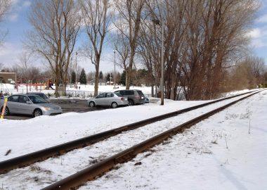 Une voie ferrée près d'un stationnement l'hiver.