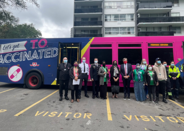 A lineup of people with medical masks on standing in front of a transit bus in a parking lot.