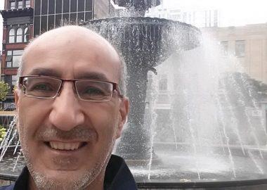 Wadih souriant devant une fontaine
