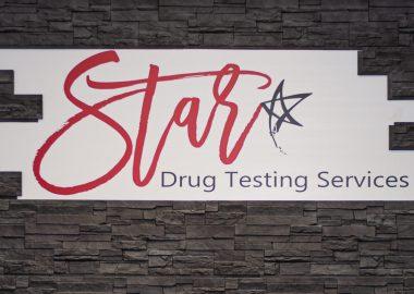 Bannière blanche sur un mur noir de la clinique Star Drug Testing