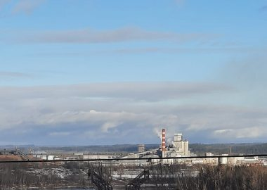 An image of a pulp mill in the distance.