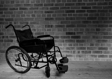 A black and white photo of a wheelchair next to a brick wall.