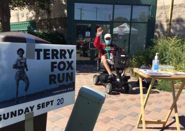 Will Dwyer envois la main à l'extérieur derrière une pancarte de Tery Fox
