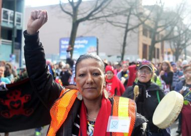 Cintesapa Taweya (aka Juanita Desjarlais) stands with her fist in the air with people marching behind her and playing drums