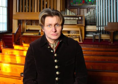 Xaver Varnus stands with his newly installed pipe organ in a church