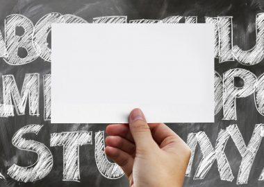 Tableau noir et lettres de l'alphabet et une main qui tient une carte blanche