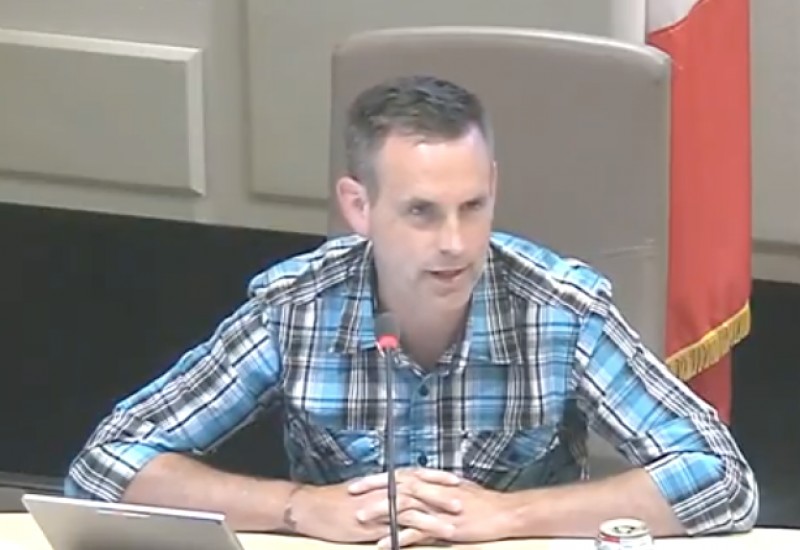 Andrew Black sits at a white desk during a Sackville town council meeting with a Canadian flag behind him and a lap top and microphone in front of him