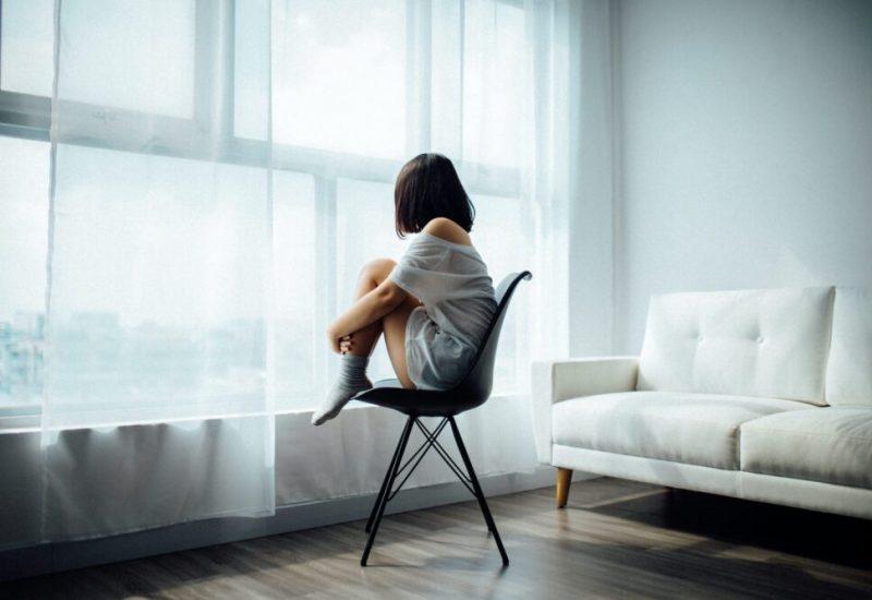 Une jeune femme, accroupie sur une chaise blanche, regarde par la fenêtre.